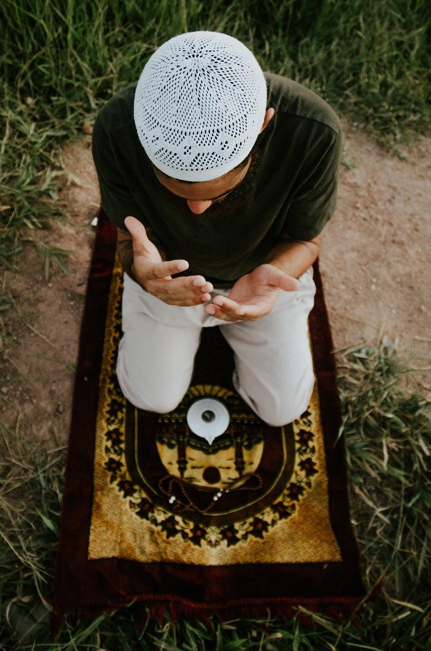 faceless man praying on carpet in field
